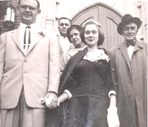 A bride and groom stand outside the church doors holding hands. The bride wearing a black dress and white gloves.