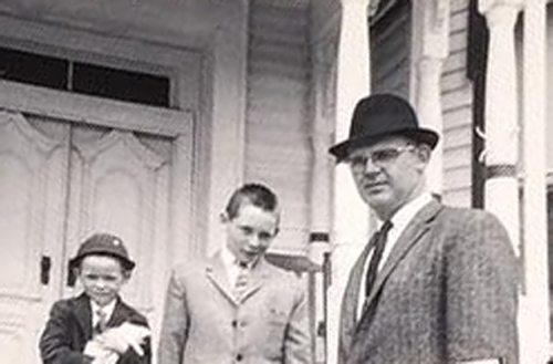 A father and two sons stand on their front porch dressed in suits.