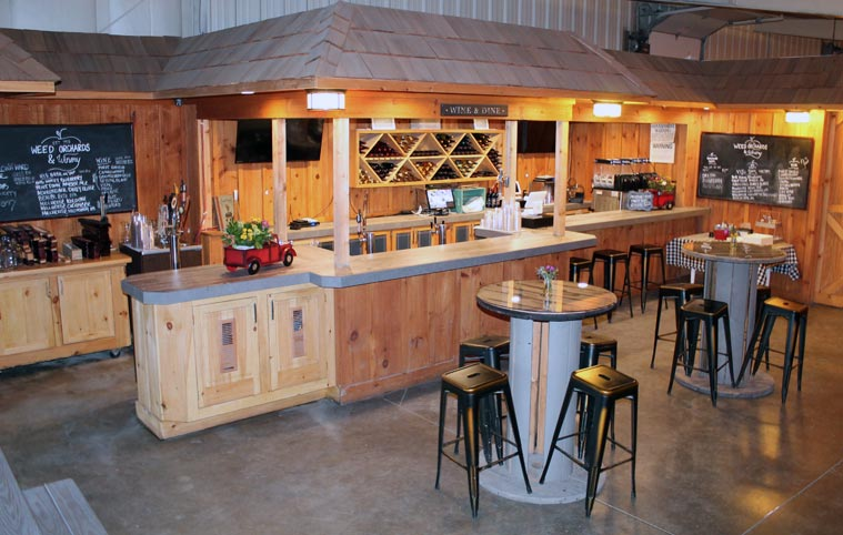 A tasting room with wood accents and soft warm lighting. Tall tables with stool benches are in the center of the room.