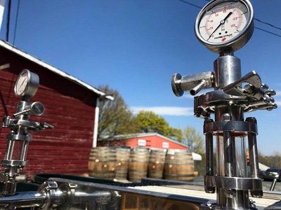 A close up of a metal wine filter with wine barrels in the background