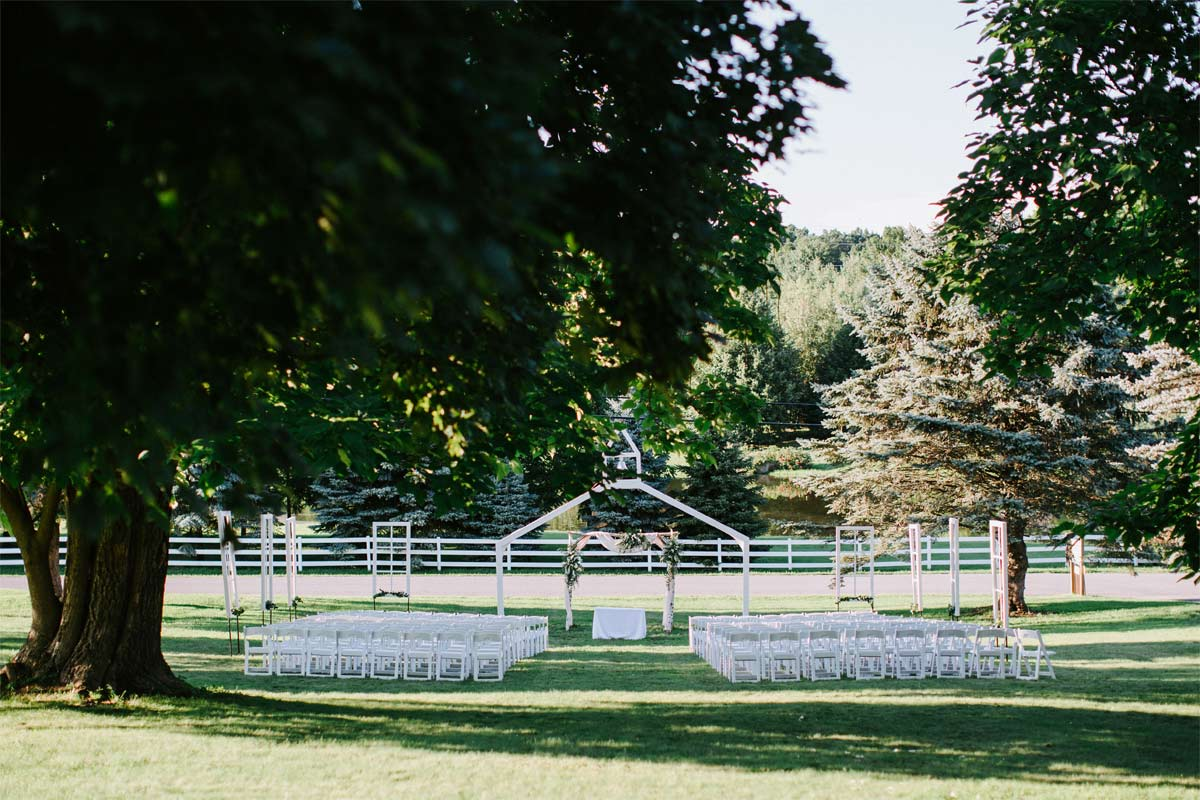 A chapel steeple centered in front of two aisles of chairs on a green lawn.