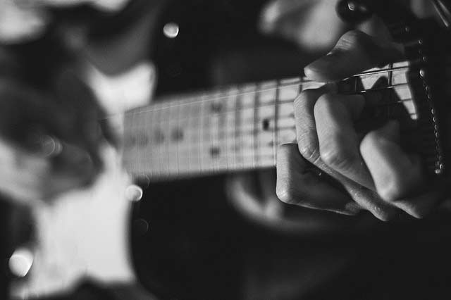 Close up of hands playing guitar