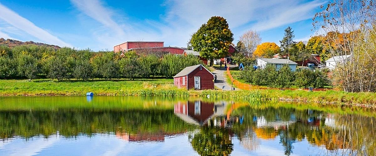 Lake with blue skies and a red barn