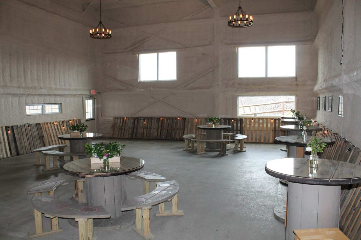 The Private Party room with circular round tables, concrete floor and high ceilings.