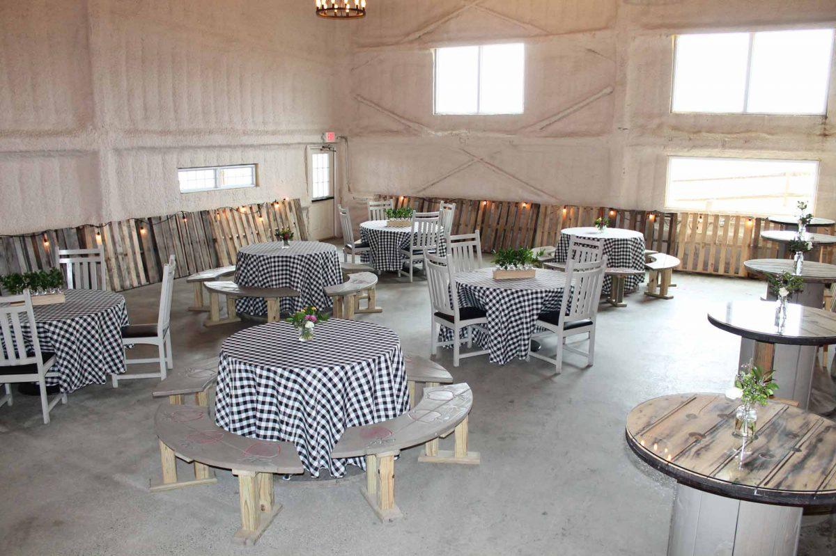 The room is staged with black and white checkered tablecloths covering the tables with bright light coming through the windows.