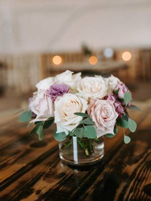 A flower arrangement of peach, ivory and pale purple flowers on a chestnut wood table.