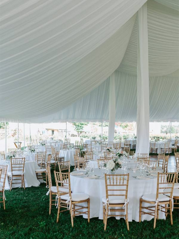 Tables with white tablecloths, and bamboo chairs under a fabric draped reception tent.