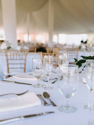 Table setting of white linens and crystal glassware.