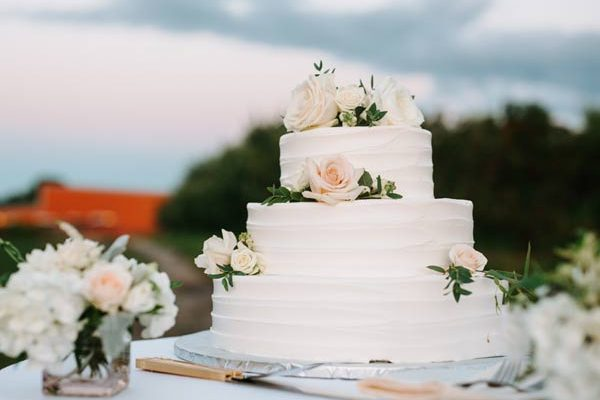 A three their wedding cake with peach roses on alternating tiers.