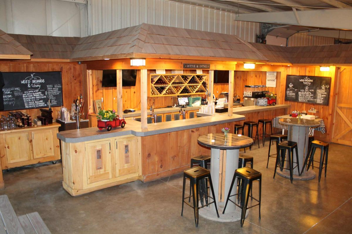 A view from the winery's entrance shows a wooden bar, warm lighting, and tall bistro style tables in the center area