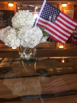 An American flag sits on a table with white hydrangeas.