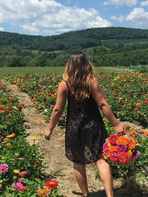 A woman is shown from the back holding a basket of flowers while walking on a path in between rows of zinnias.