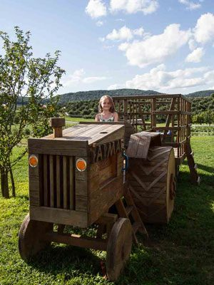 A small child pretends to steer a giant wooden tractor