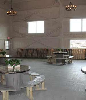A small thumbnail of a while walled venue with wooden tables